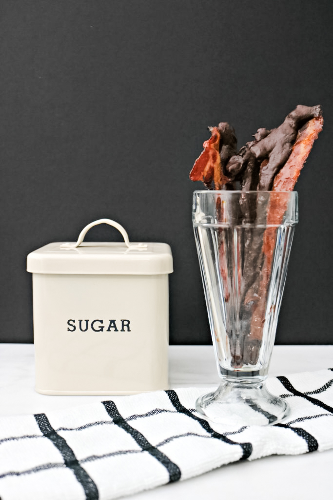 A milkshake glass holds chocolate-covered bacon and sugar and maple syrup and a striped napkin are shown.
