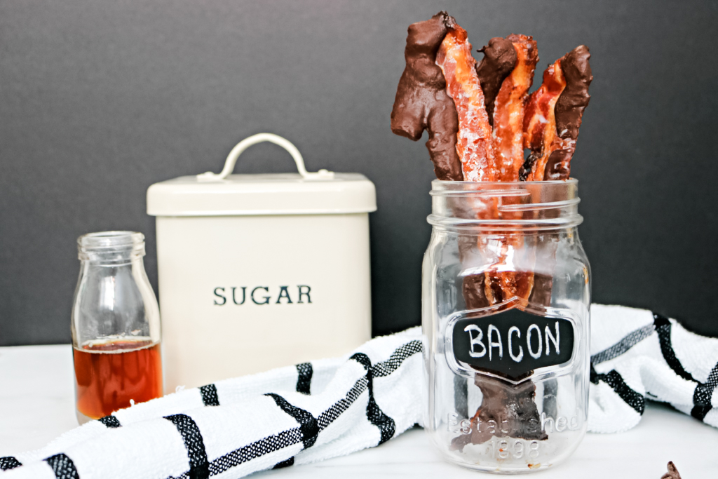 A mason jar holds chocolate-covered bacon and sugar and maple syrup and a striped napkin are shown.