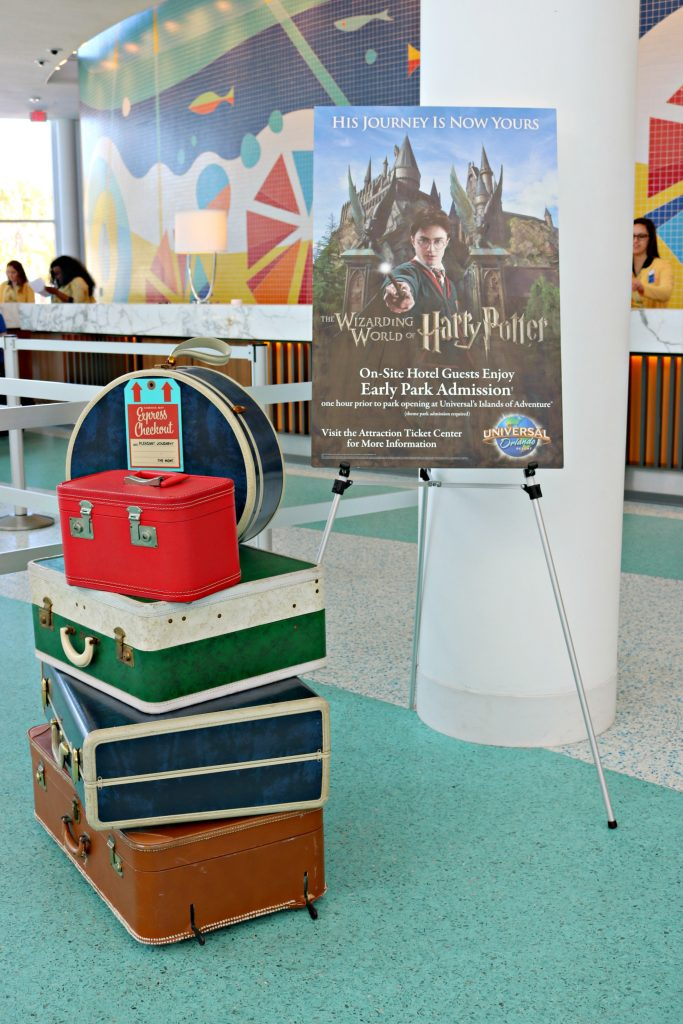 A sign with the Wizarding World of Harry Potter sits next to vintage luggage.