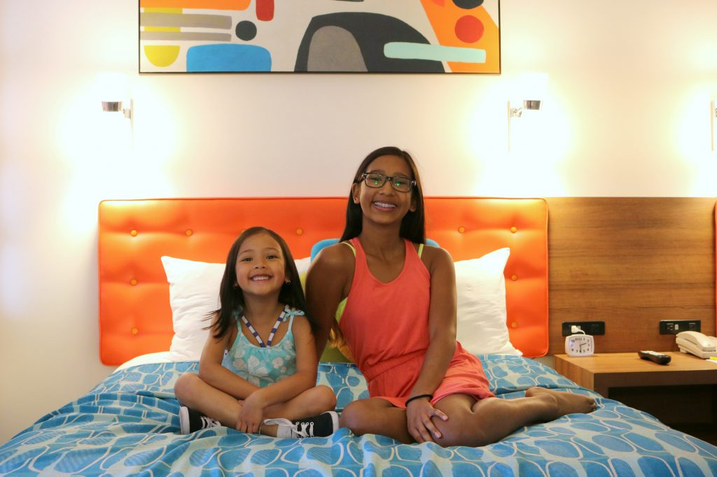 The girls sit on one of the beds inside the family suite at Cabana Bay Beach Resort.