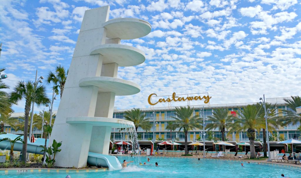 The Castaway Bay Beach Resort fountain, pool, and slides against a beautiful blue sky.