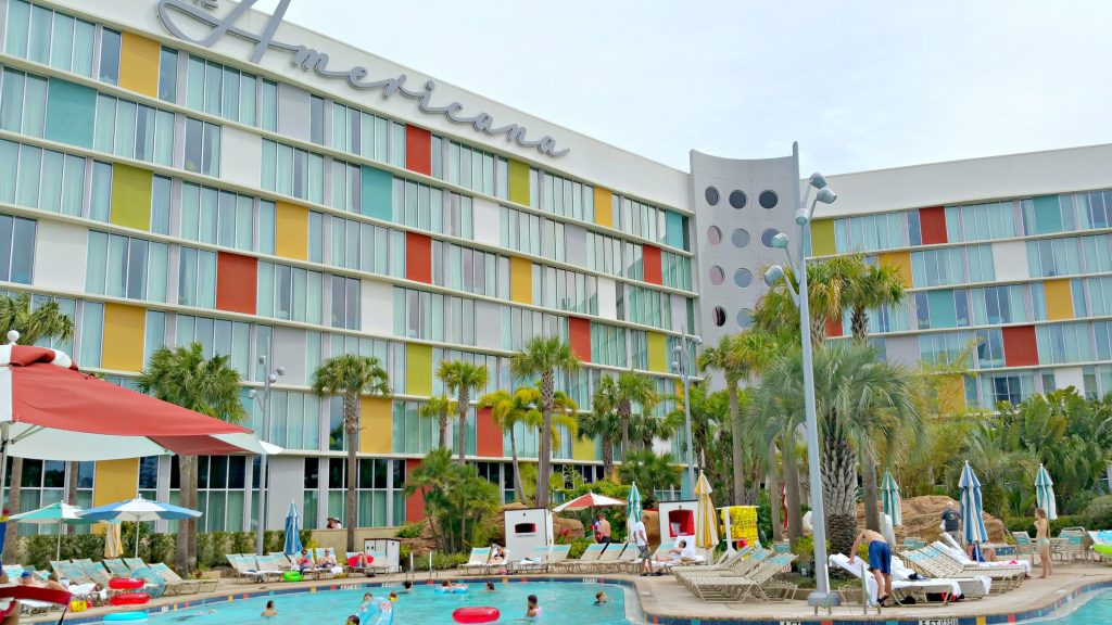 The American side of the Cabana Bay Beach Resort with guest swimming in the pool.