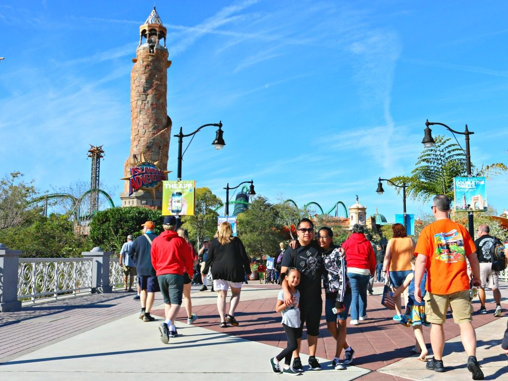 Family stops to pose in front of Island of Adventure tower.