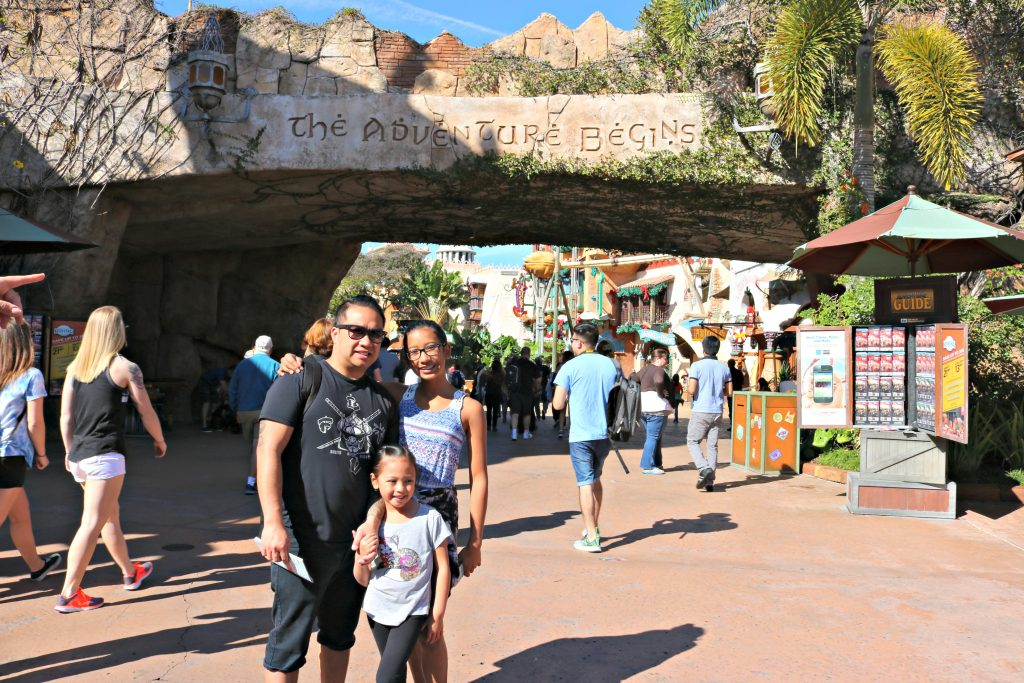 A family poses in front of the entrance of Island of Adventure at Universal Studios.