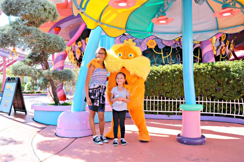 Two girls pose with the Lorax and smile.