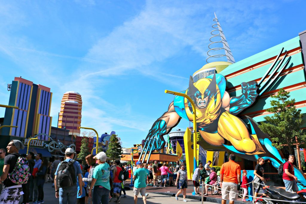 People stand in front of a giant Wolverine on a building at Universal Studios.