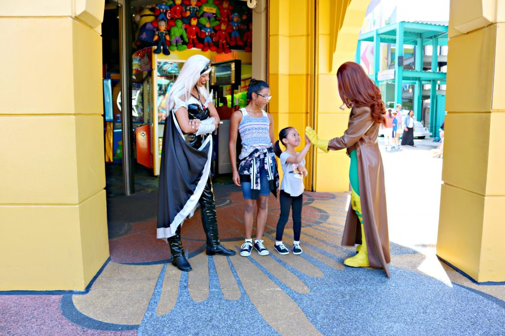 A little girl high-fives Rogue from X-Men while Storm watches on.