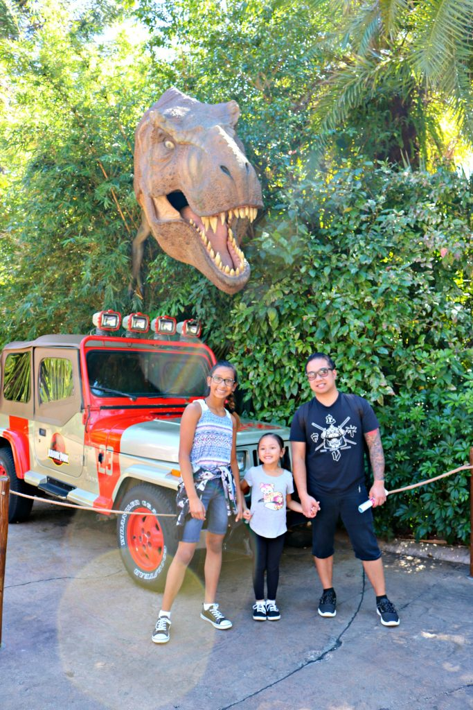A dad and his two girls stand in front of a Jurassic Park Jeep and a T-Rex pokes its head out of the trees.