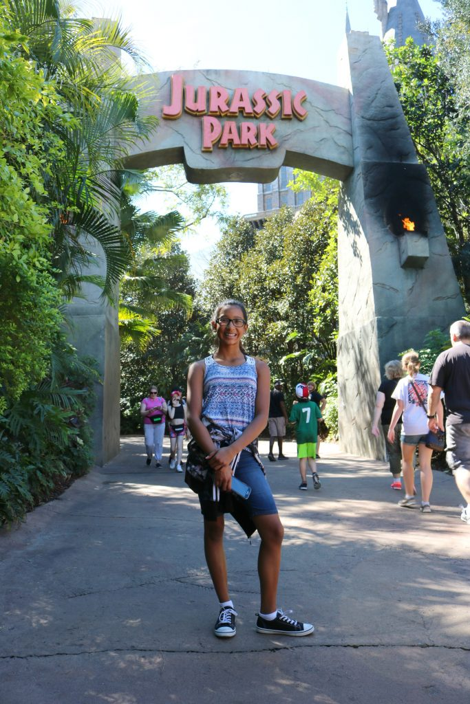 A girl stands in front of the Jurassic Park gate.