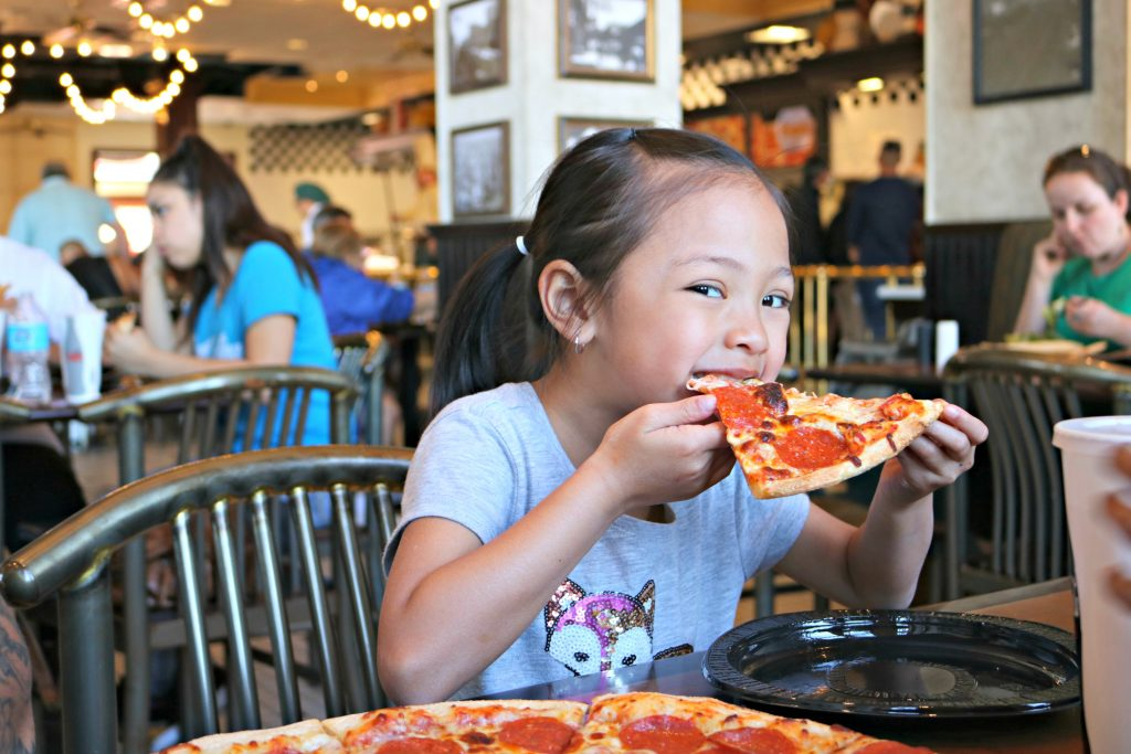 Little girl bites into a big slice of pizza at a restaurant at Universal Studios.