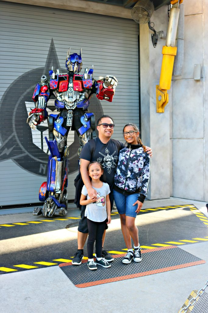 A dad and his two girls pose with Optimus Prime.