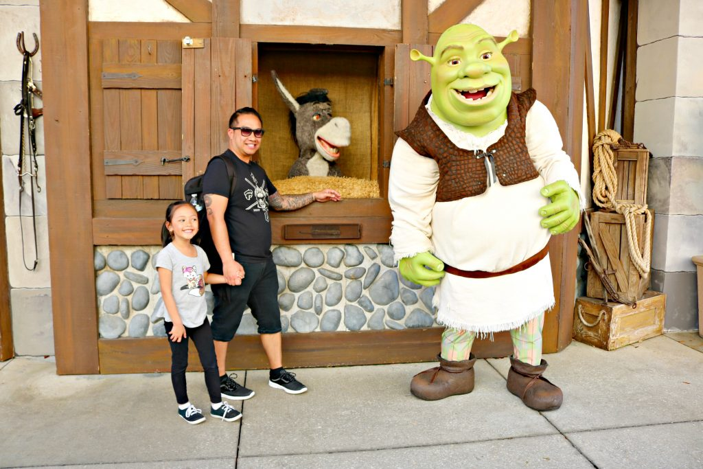 A girl and her dad pose with Shrek and Donkey.