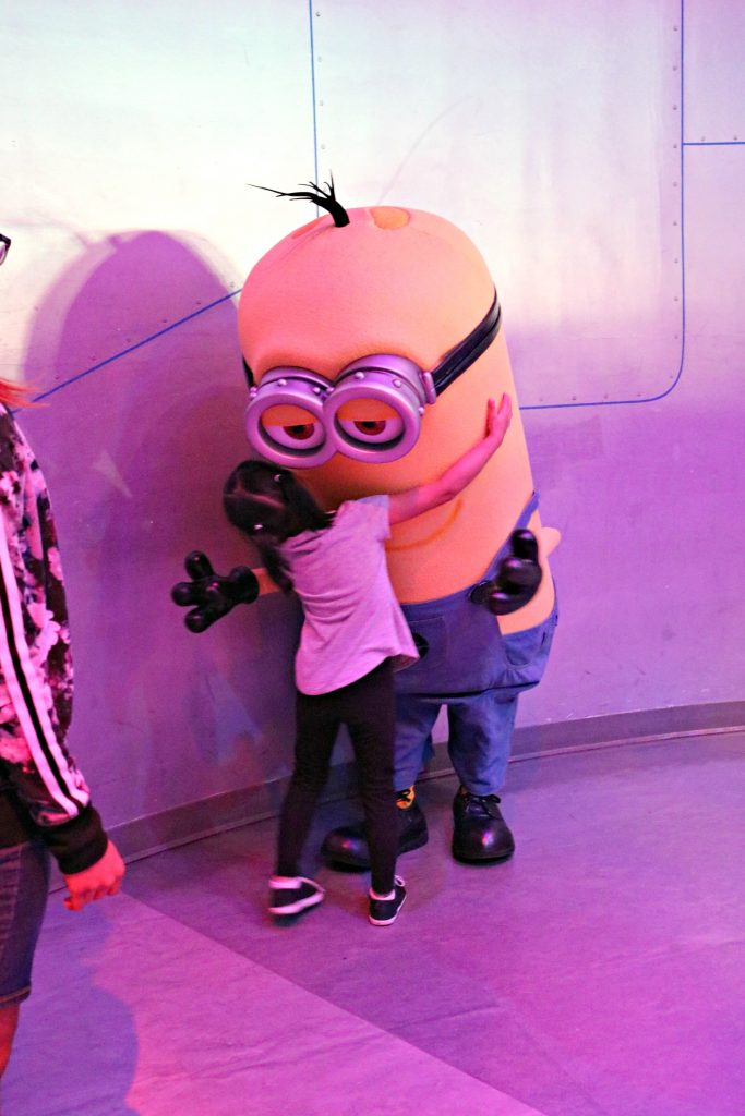 A little girl hugs a minion from Despicable Me.
