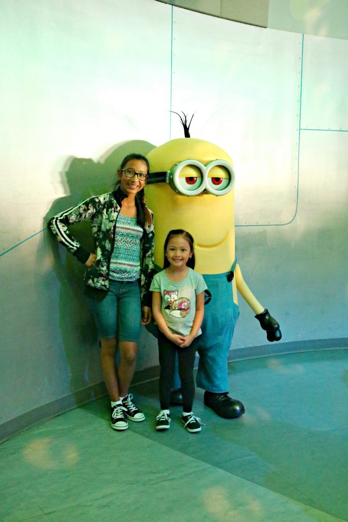 Two little girls pose with a minion from Despicable Me.