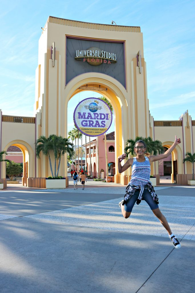 A young girl jumps in front of the Universal Studios entrance.