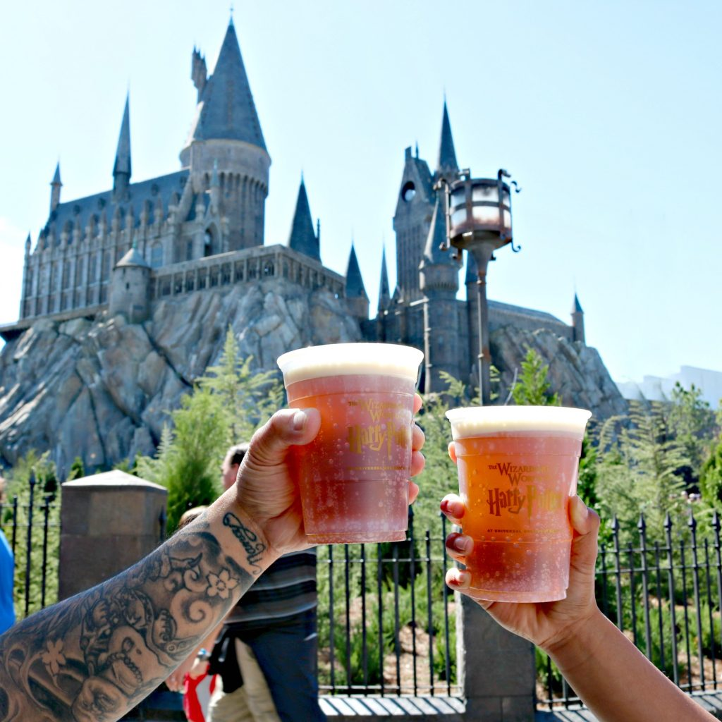 Two people hold butterbeer and do cheers in front of Hogwarts Castle.