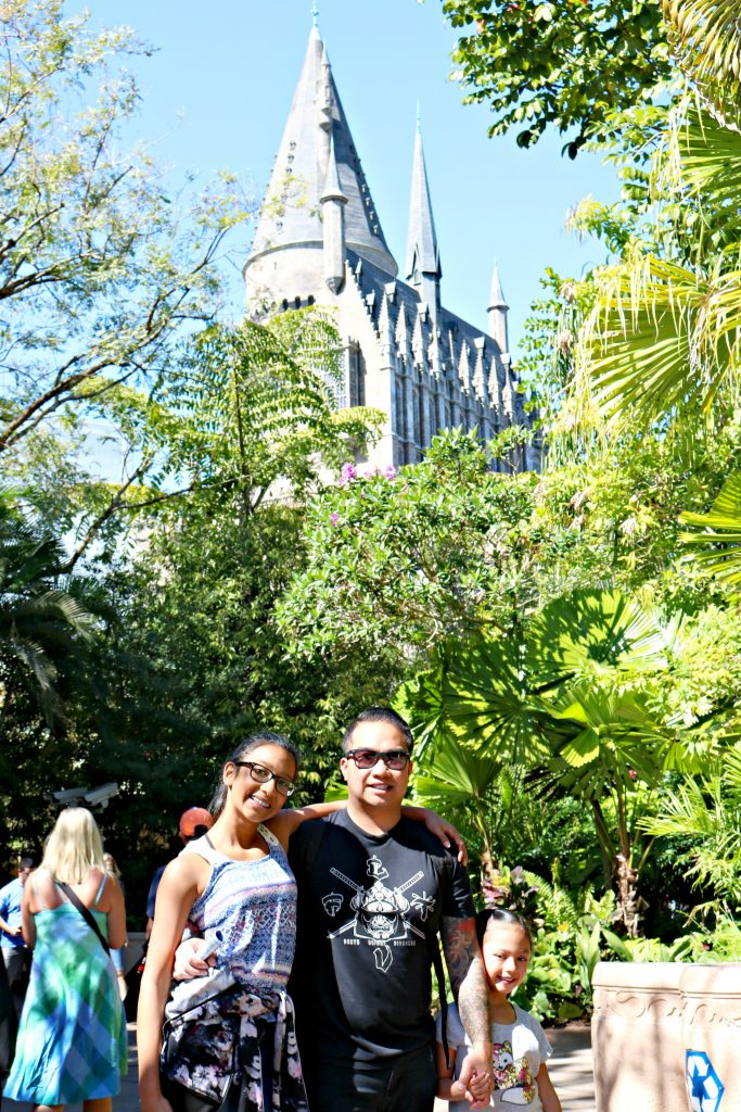 Two girls and her dad pose at Universal Studios, Hogwarts Castle is seen in the distance.