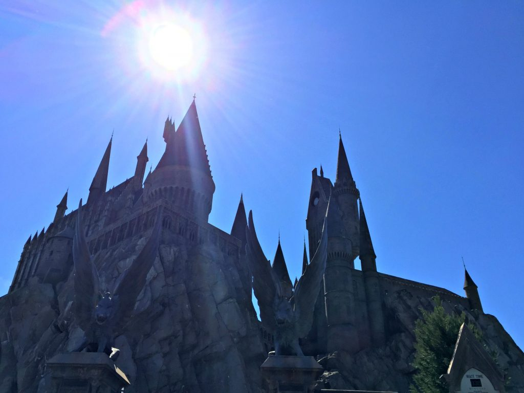 The sun shines bright and high in the sky at Hogwarts Castle.