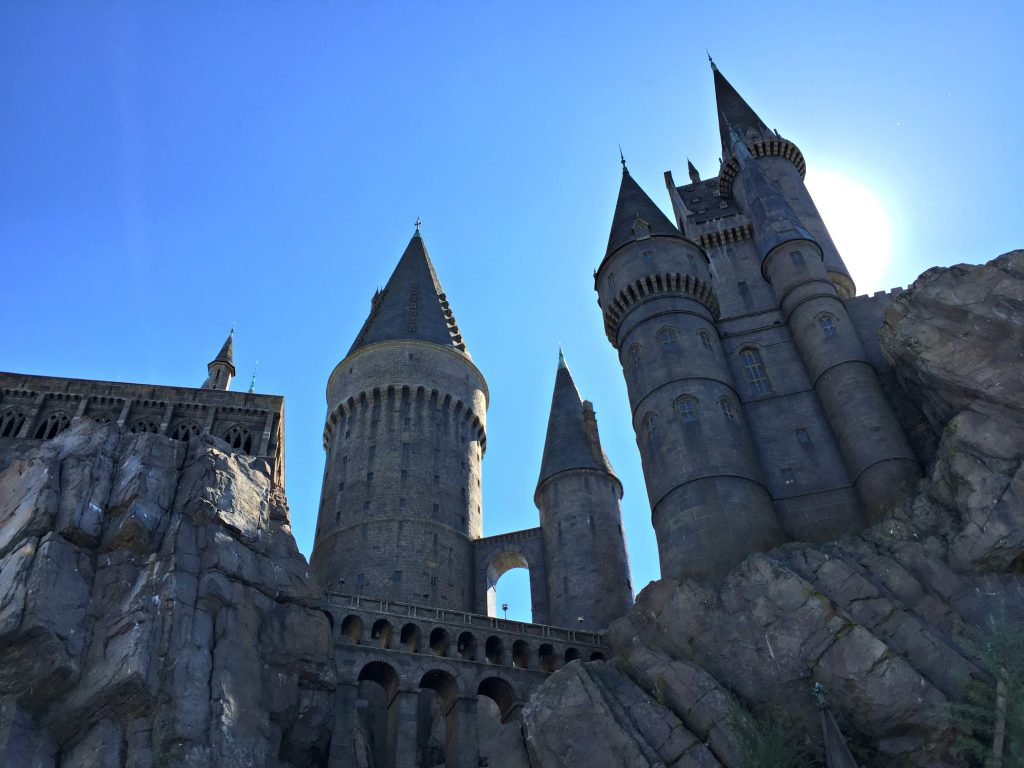 Hogwarts Castle with a blue sky and sun in the sky.