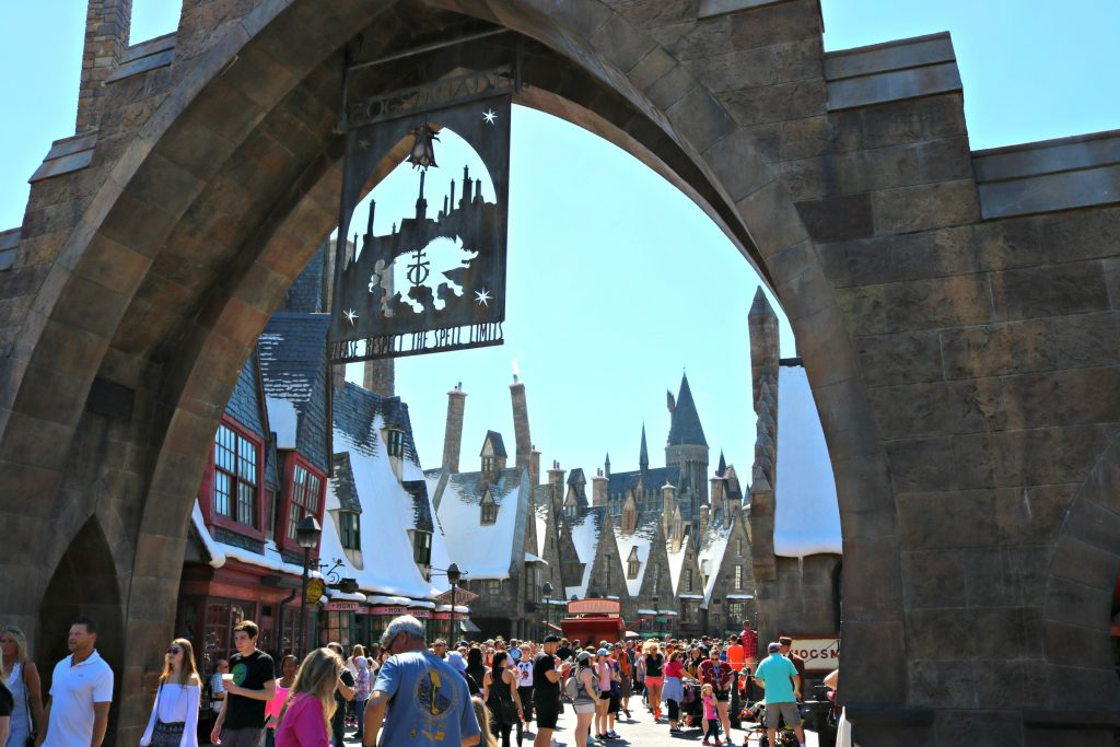 The sign of Hogsmeade and the people enjoying it.