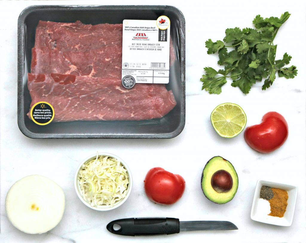 Cooking ingredients flat lay of beef, cilantro, onion, tomatio, avocado, spices, and more.