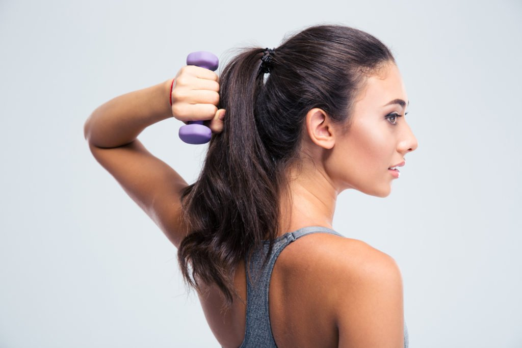 Side view portrait of a beautiful sports woman working out with dumbbells isolated on a white background.