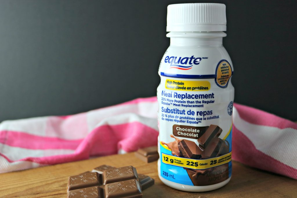 Equate Meal Replacement, in Chocolate flavour. There's a striped white and pink napkin behind it, on a wooden board with chunks of chocolate.