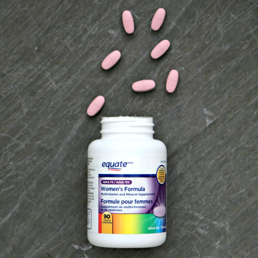 An Equate bottle of Women's Formula is laying flat, pink pills are spilling out.