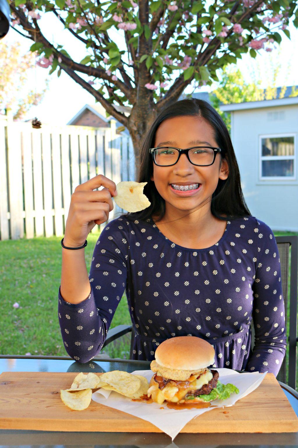 Gabby eats a potato chip while she enjoys the Maple Bacon Poutine burger. She smiles.