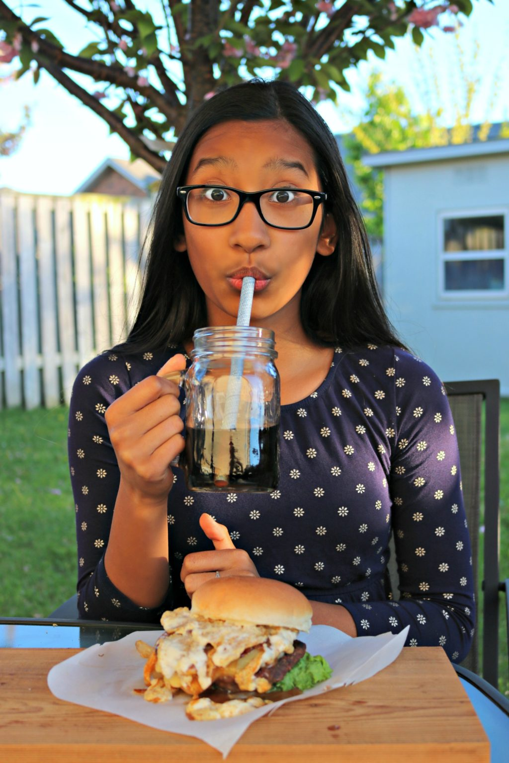 Gabby take a sip of her soda, her eyebrows are raised in shock at how good the burger is.