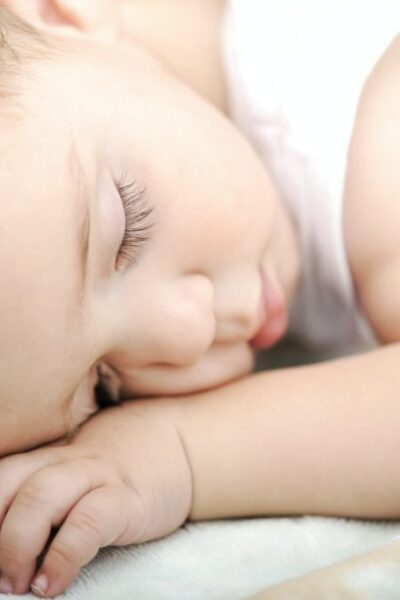 A baby sleeps on his stomach. The baby looks peaceful and has long eyelashes.
