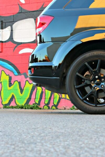 A Dodge Journey is parked in front of a graffiti wall, only the back end is seen.