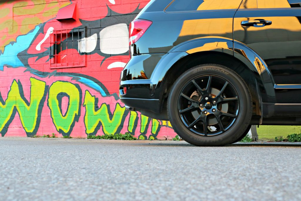 A Dodge Journey's bottom half is shown in front of a graffiti wall. These are 7 tips for buying a vehicle.