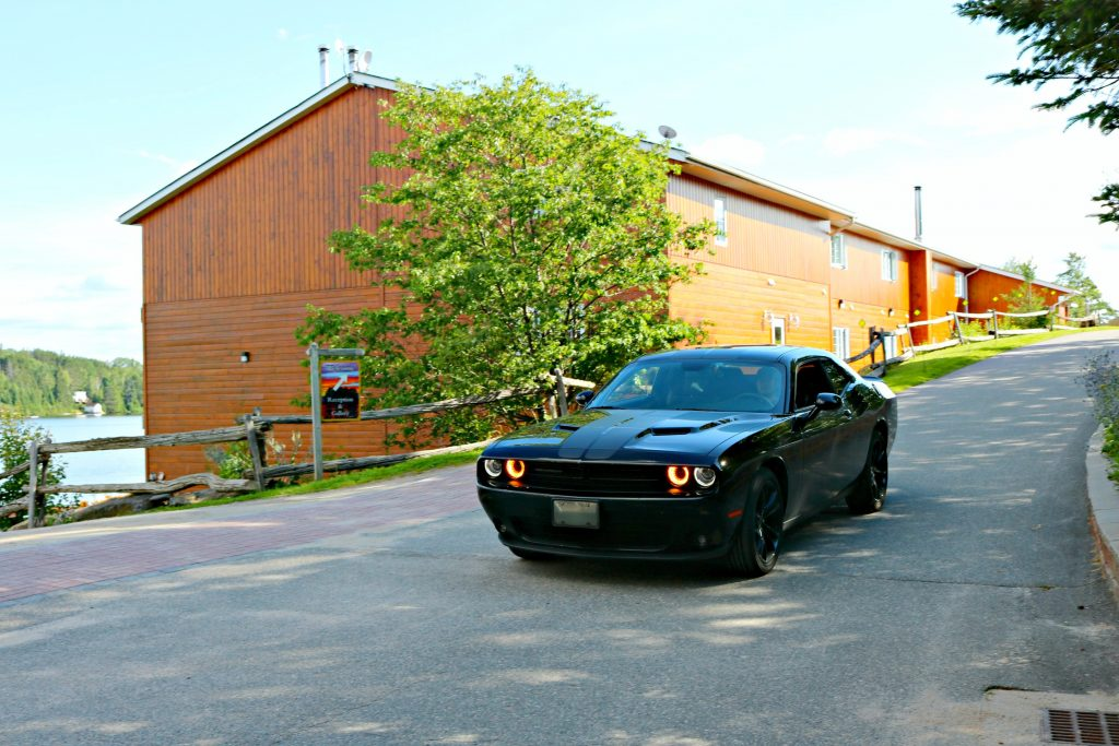 A Dodge Challenger is pictured coming down the drive, cabins are pictured behind it.