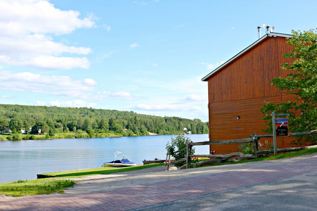 A cabin at Couples Resort outlooks the beautiful greenery and lake.