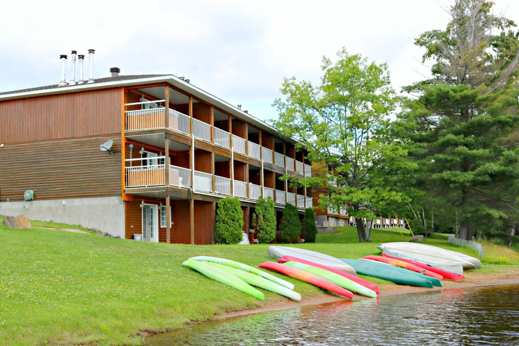A building with balconies with private hot tubs are shown. It is right by the water and canoes are docked.