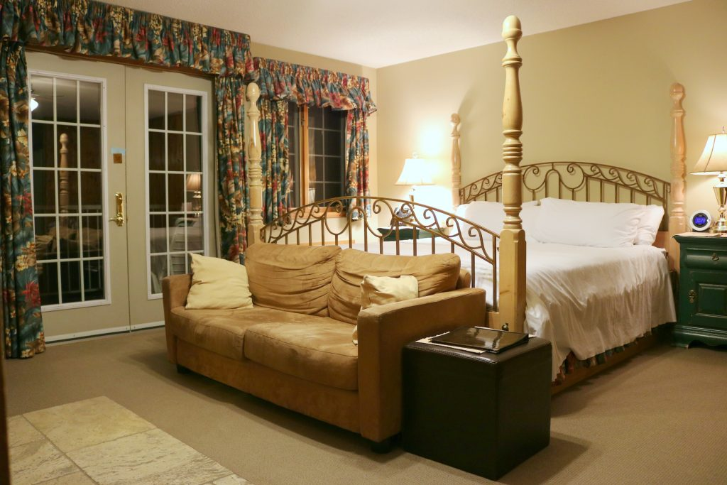 A beautiful king size bed is shown with a loveseat at the end of the bed. It's styled in a traditional old world style.