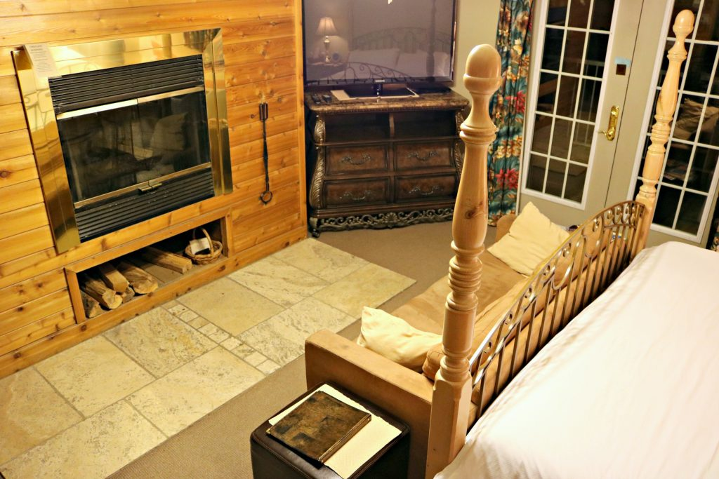The same bed is pictured and a wood burning fireplace is shown next to a tv stand.