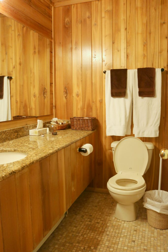 The bathroom is wooden blanks also, very rustic and a toilet and sink are shown.