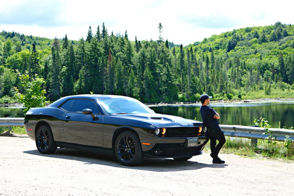Darasak leans on his Dodge Challenger while he overlooks the lake.