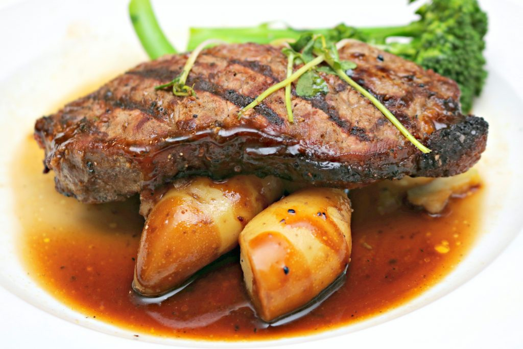 A full picture of steak with fingerling potatoes, broccolini, and aux jus.