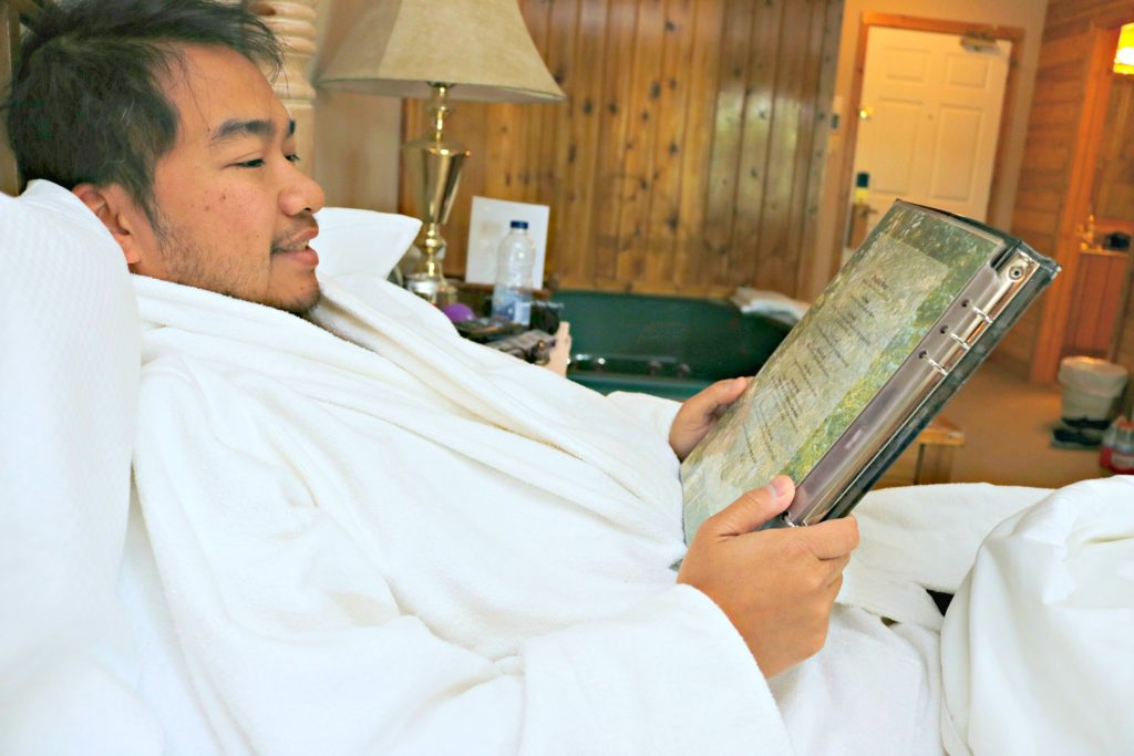 Darasak is in a robe in bed and looks at the room service menu.