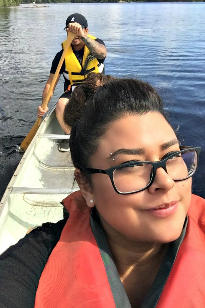 A wife and husband canoe on the lake, the wife takes a selfie and the husband paddles.