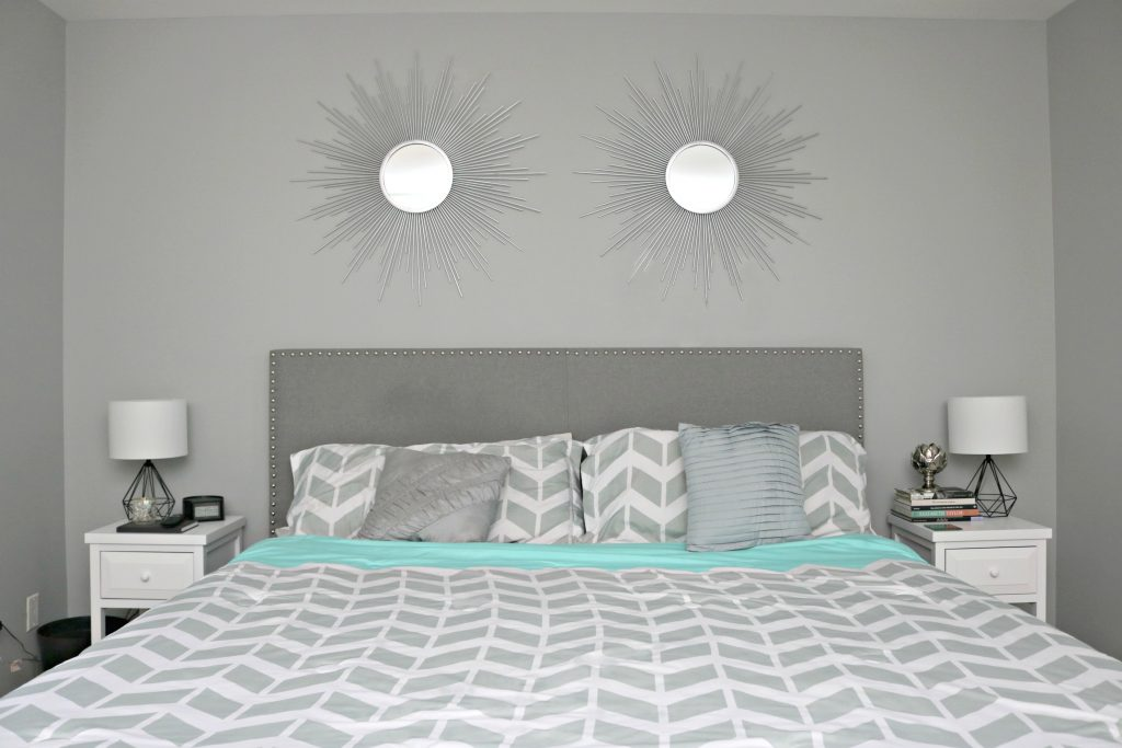 The bed is shown with herringbone sheets in grey and teal, with decorative pillows and two night stands.