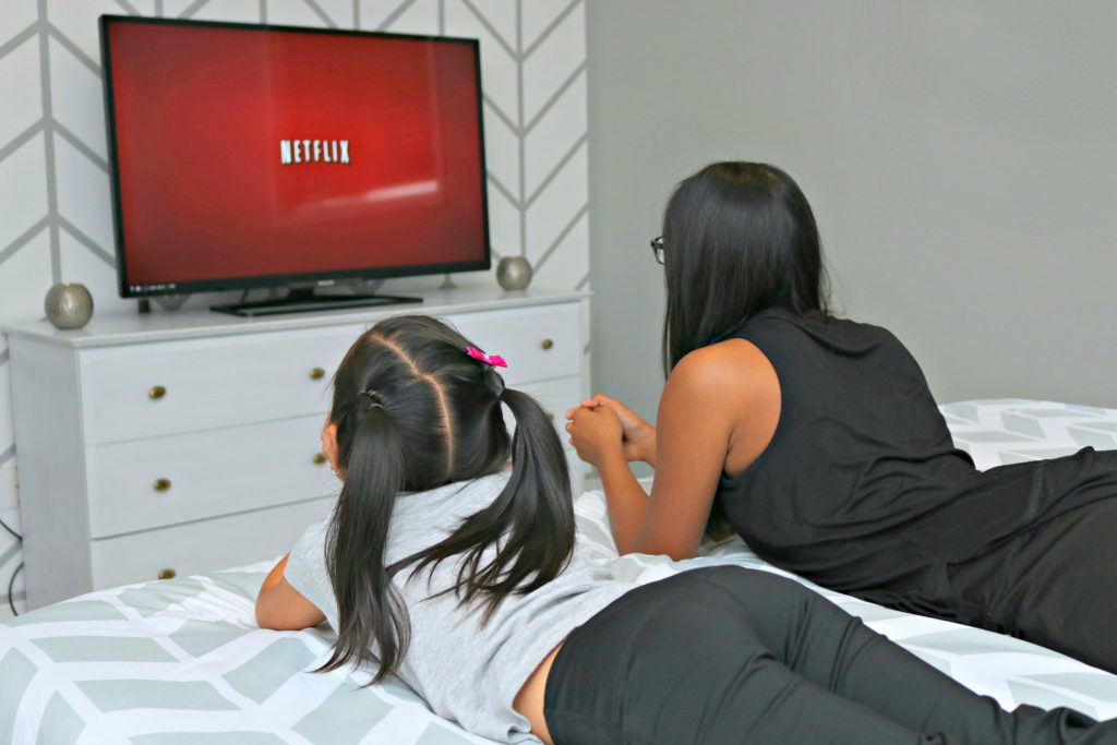 Two girls lay on their tummies and watch the screen as Netflix loads.