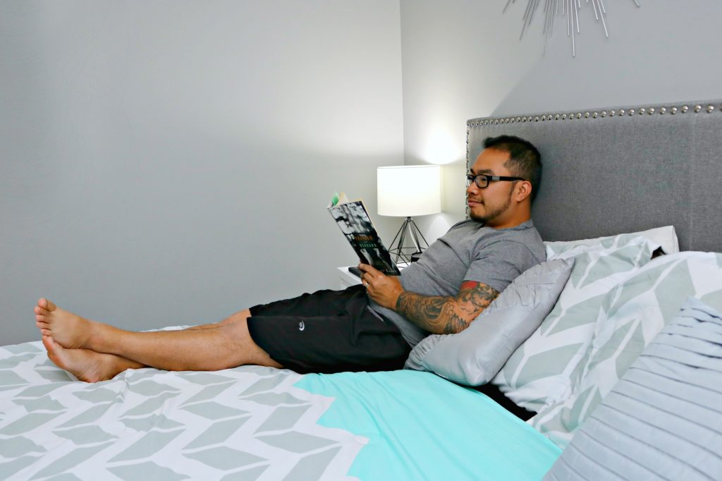 A man reads a book and lies in his bed relaxing.