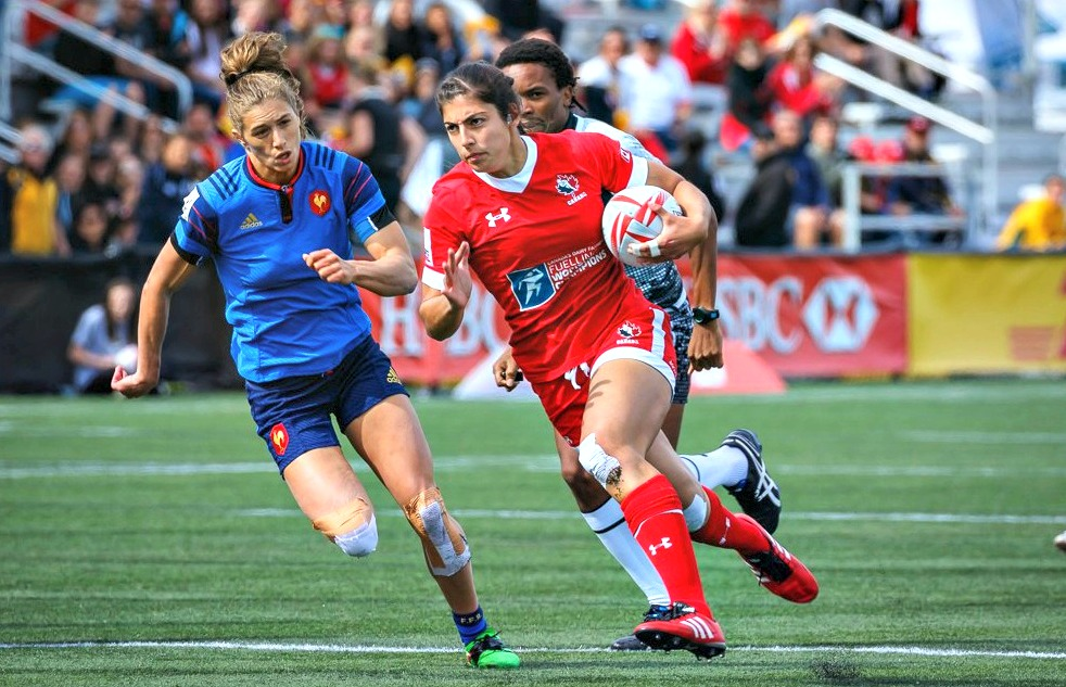 Two women play rugby.
