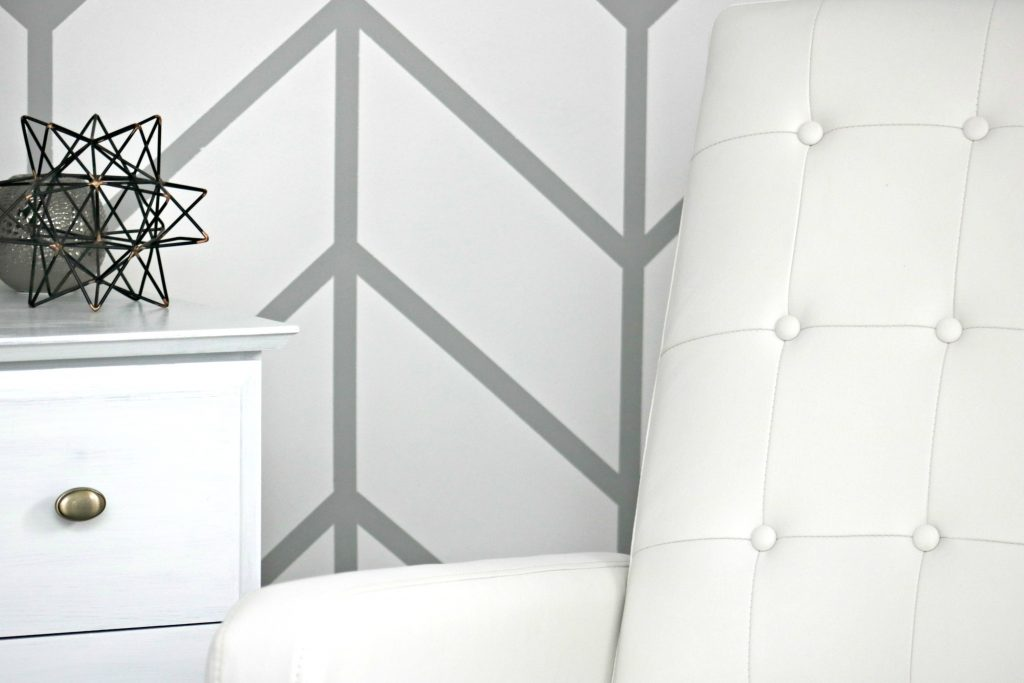 White recliner against a herring bone painted wall. A white dresser is shown along with some geometrical decor on dresser.
