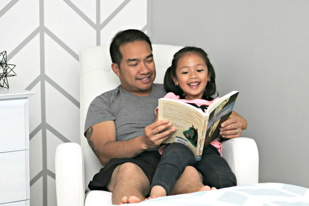 Mimi and Darasak laugh while they read a book on the recliner from Best Buy.
