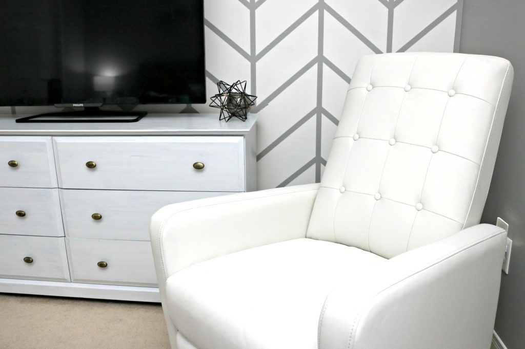 Side view of white recliner against herringbone wall, dresser, and TV. All bought in the Best Buy Baby Sale.